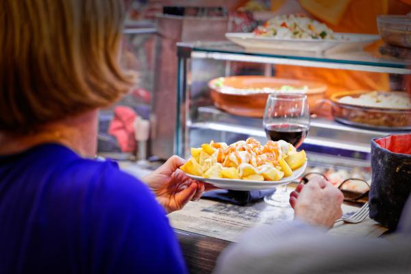 Frau isst an einem Stand auf dem La Boqueria Markt