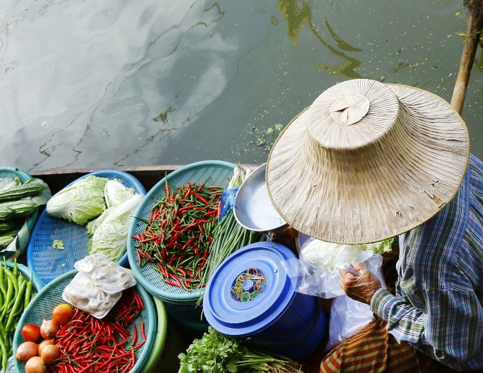 Woman trading fruit and food in boats at Damnoen Saduak floating market ,Thailand