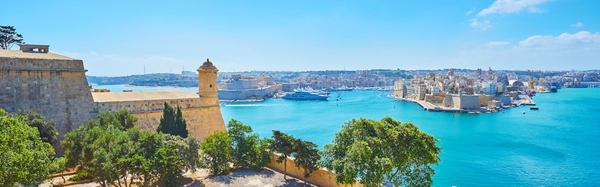 Medieval fortified cities of Birgu and Senglea, surrounded by blue waters of Grand Harbour with small tower of St Peter and Paul counterguard on the foreground, Valletta, Malta.