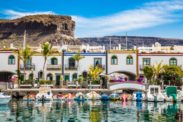 Traditional Colorful Buildings With Boats In Front And Mountain In The Backsground - Puerto de Mogan, Gran Canaria, Canary Islands, Spain
