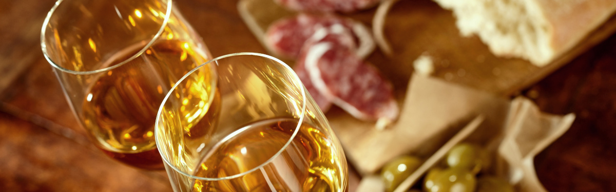 Two glasses of sherry with traditional Spanish tapas of olives, salami and a fresh loaf of bread with selective focus to the drinks