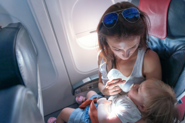 Young mother feeding her small daughter from bottle on airplane
