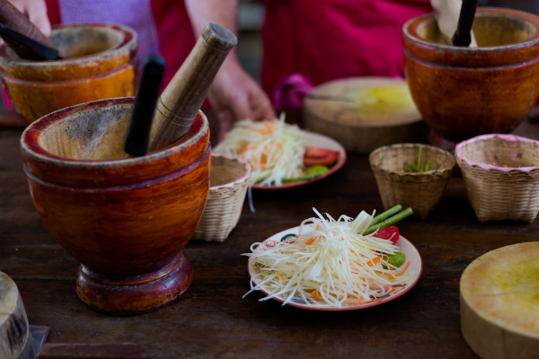 Spicy papaya Som Tam salad ingredients and wooden mortar. Picture of traditional thai cuisine made of fresh ingredients taken during cooking class in Chiang Mai.