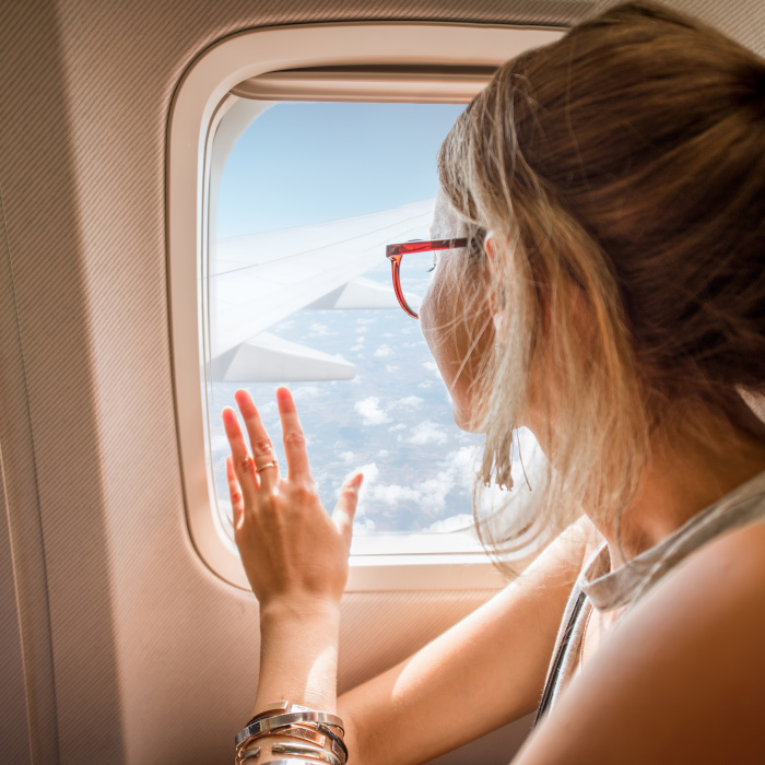 Young woman enjoying the view through the aircraft window sitting during the flight in the airplane
