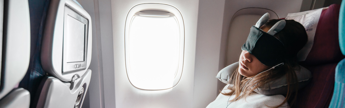 Teenage girl sleeping on boad during flight. Young passenger travelling by airplane alone.