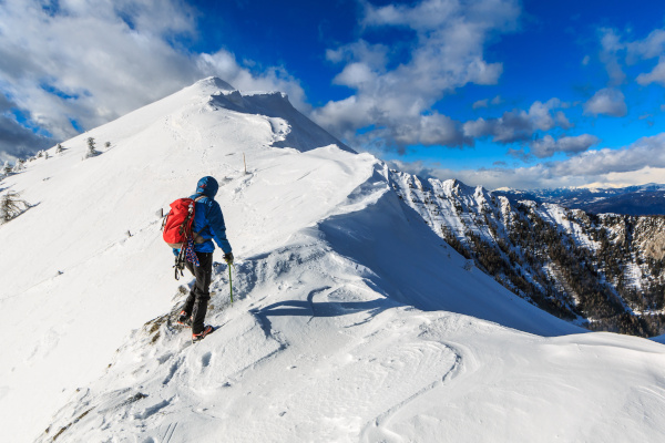 Mountaineer walking on the snowy slope of theDovska Baba mountain in Karavanke range, Slovenia