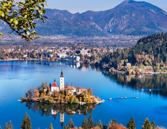 Bled, Slovenia - Panoramic aerial view of Lake Bled with Church of the Assumption of Maria, traditional Pletna boats at autumn background